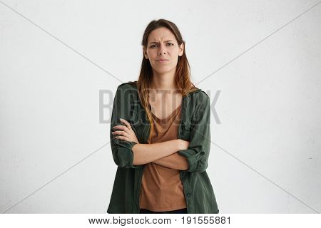 Portrait Of Aggravated Sad Woman With Long Face And Healthy Skin Standing Crossed Hands Expressing H