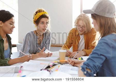 Four Mixed Race Students Dicussing Something While Sitting With Books Indoors Deciding How To Make P