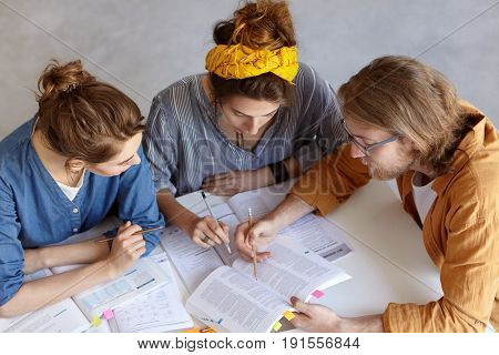 Portrait Of Two Girl And One Man Sitting Indoors Studying Reading Books Discussing Main Problems Tog