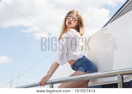 Beautiful blonde girl in shorts and t-shirt posing around the yacht, pier, sea port