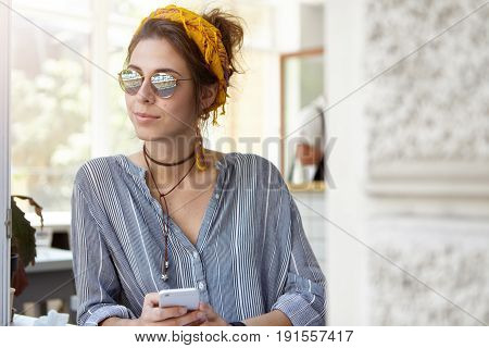 Trendy Young Woman In Shades And Yellow Headband Leaning At Table Holding Mobile Telephone Standing