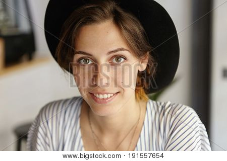 Close-up Of Glamour Young Female With European Appearance Wearing Black Hat And Stripped Blouse Look