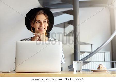 Pensive Woman With Attractive Appearance Wearing Black Hat Sitting At Table With Laptop, Having Deep