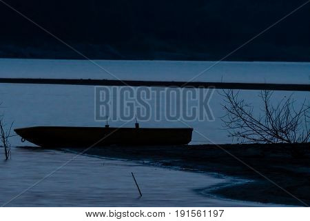 Silhouette of a fishing boat on a sandbar in a river taken after sunset