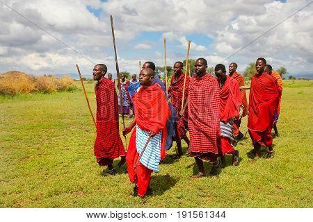 Africa Tanzania Masai village - March 04 2016: Masai men in colorful clothes perform a ritual dance
