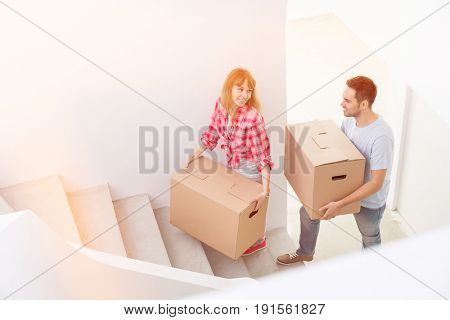 Happy couple carrying moving boxes up stairs in new house