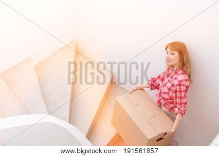 Portrait of beautiful woman carrying cardboard box