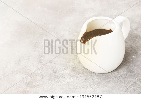 The Melted Chocolate (chocolate Sauce) In A White Sauce-boat On A Light Background. Toning