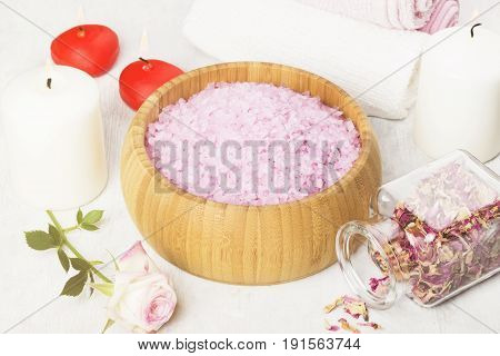Bath salt with aroma of a rose in a wooden bowl petals and a fresh pink rose towels and candles on a white background. Toning