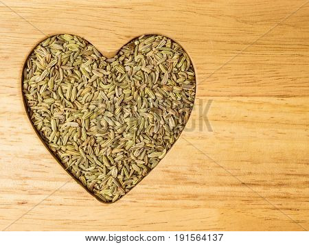 Dried fennel dill seeds heart shaped on wooden surface with copy space
