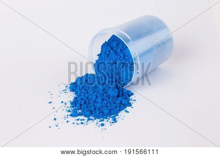 pigment on a white background, blue pigment in a bottle