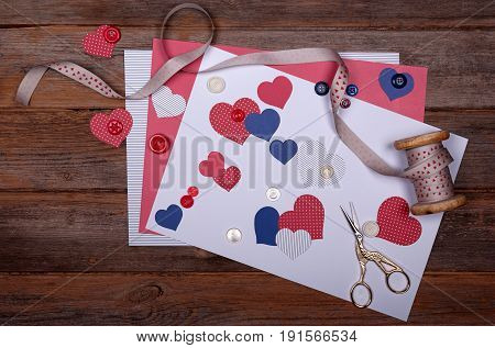 Selection of scrapbook papers, card, shapes like hearts, buttons, ribbon and scissors on wooden background with a vintage feel. Can be used for making a scrapbook page for special occasions like Independence Day.