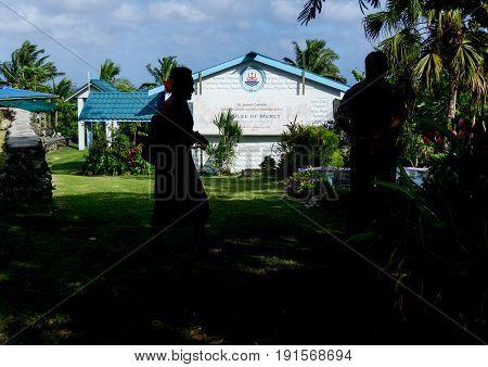 Alofi, Niue - May 29, 2017; Silhouettes of two Pacific Island people figures standing in cool of shade waiting to enter Saint Joseph's Catholic Church Alofi Niue