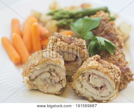 Chicken cordon blue with vegetables on a white plate close up