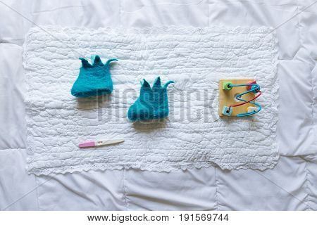 Baby Shoes With Toys And Pregnancy  Test On White Background