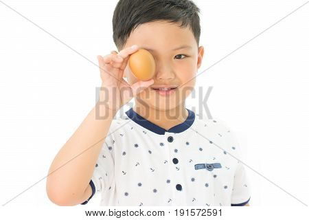 Asian boy shutting eye with hen egg isolated on white background