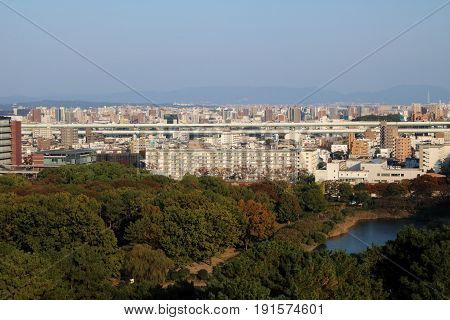 Aerial view of Nagoya city center at dusk with Meijo lake and Autumn foliage in the foreground Aichi Prefecture Japan