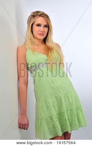 Beautiful teen girl model wearing a green dress on a neutral background