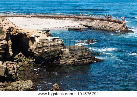LA JOLLA, CALIFORNIA - JUNE 16, 2017:  Eroded sandstone cliffs near the historic La Jolla Children's Pool, with concrete sea wall built in 1931 to protect swimmers from the ocean waves.