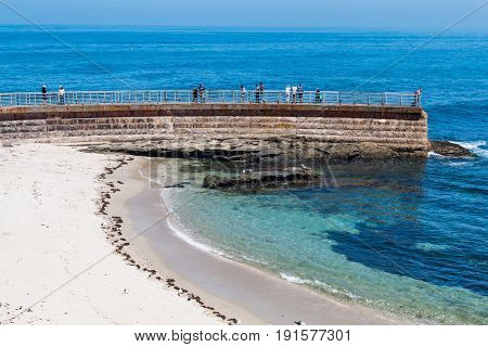 LA JOLLA, CALIFORNIA - JUNE 16, 2017:  People on the sea wall overlooking the Children's Pool.  The wall was built was a protective barrier from the ocean waves in 1931.