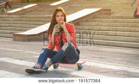 A teenage girl drinks fruit fresh and sits on a skateboard. A breather after skateboarding. Active way of life in urban space. Youth fashion.