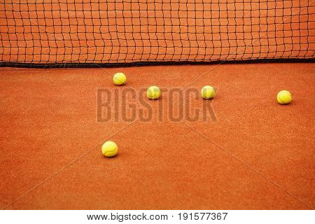 Five yellow tennis balls lie on the tennis court near the net. The concept of sport.