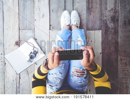 Hipster lifestyle - Girl in jeans with black smartphone and retro camera sit on the wooden floor. vintage film color effect and retro color style