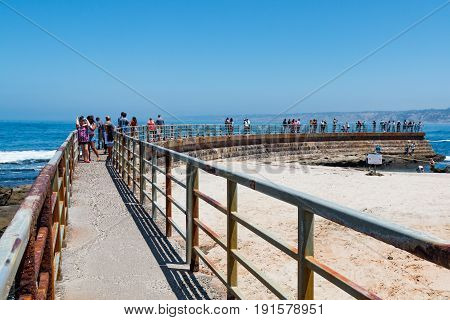 LA JOLLA, CALIFORNIA - JUNE 16, 2017:  Concrete sea wall built in 1931, providing visitors an overlook to view the Children's Pool, a site frequented by harbor seals and sea lions.