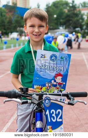 KAZAKHSTAN, ALMATY - JUNE 11, 2017: Children's cycling competitions Tour de kids. Children aged 2 to 7 years compete in the stadium and receive prizes. excited boy and girls with medals.