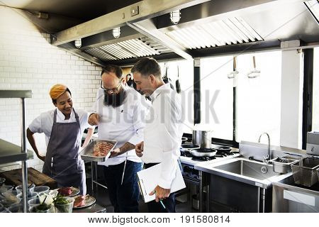 Chef showing a raw meat to a man