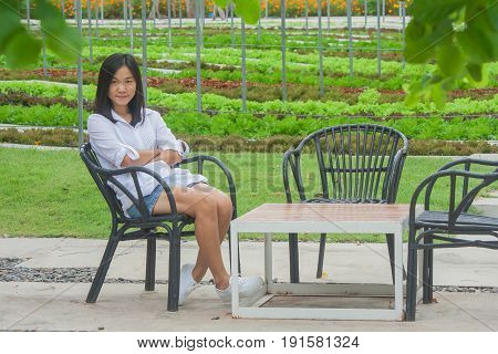 Relaxation Concept : Woman relaxing on wooden chair at outdoor garden surrounded green natural. (Autumn filter effect)