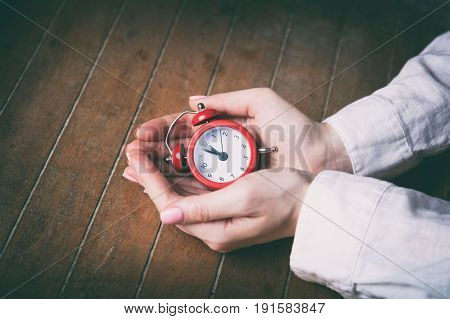 Young Woman Hands Holding Red Alarm Clock