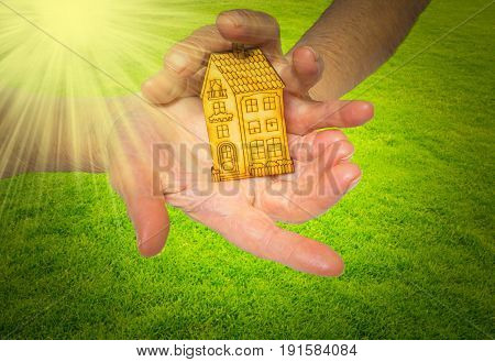 The bright picture of woman holding wooden house on green. Concept of dream