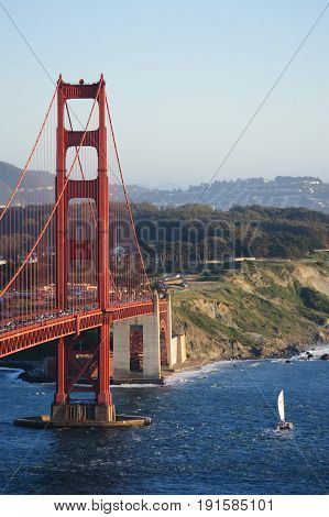 A little boat sails underneath the Golden Gate Bridge, San Francsico, during sunet.