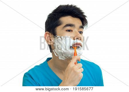 a close-up portrait of the guy with black hair and scum on the face with a razor is isolated on a white background