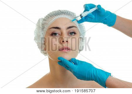 cosmetologist in gloves makes procedures on the face of a young girl have close-up isolated on white background