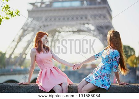 Two Friends Sitting Near The Eiffel Tower In Paris, France