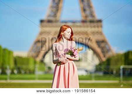 Girl With Traditional French Bread (baguette) And Flowers In Front Of The Eiffel Tower