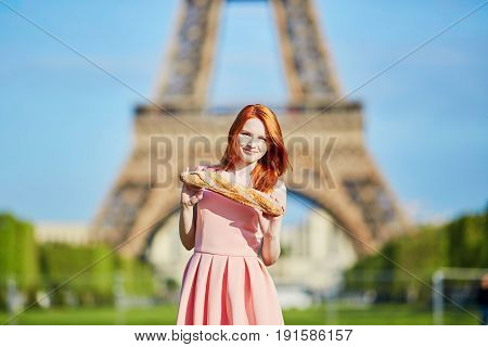 Girl With Traditional French Bread (baguette) In Front Of The Eiffel Tower