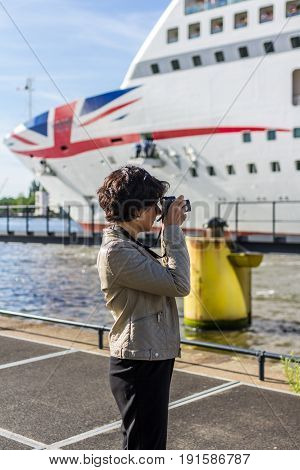 Amsterdam the Netherlands - May 31 2017: woman photographing bow of P&O Aurora cruise ship in Amsterdam