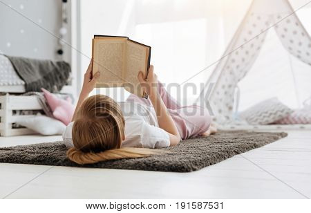 Intellectual hobby. Cute admirable bright girl stretching on the carpet and holding a book in her hands while reading it