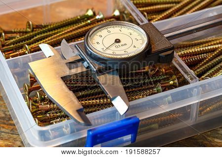 Slide Caliper With Round Scale And Screws In Storage Box On A Wooden Table
