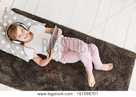 Comfortable nook. Lovely charismatic beautiful child relaxing on a rug in her room while wearing headphones and using tablet for entertaining herself