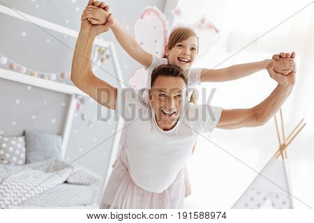 Fairies in action. Imaginative talented cute child and her father acting as fairies while plying and enjoying their time at home