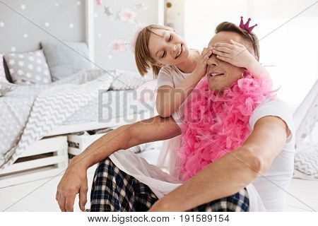 I wonder who this is. Sociable original active girl enjoying her time while dressing her father like a princess and closing his eye with her hands