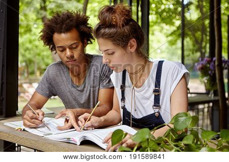 Multiracial Friends Standing Outdoor Having Look In Books Pointing Out Something Important There. Af