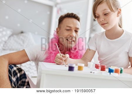 Skills of an artist. Creative imaginative gifted girl using gouache colors for drawing things while her dad watching over her