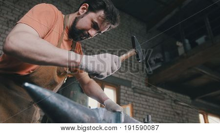 Muscular blacksmith in forge hammering steel products, small business