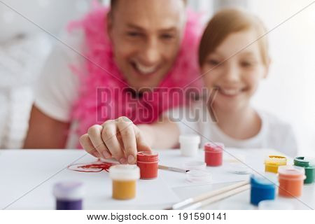 Expressive color. Incredible charismatic active family enjoying drawing together while using gouache colors and looking happy