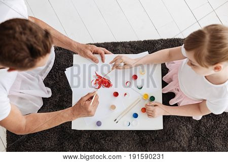 Art of unity. Artistic active imaginative girl having a creative morning and working on little masterpiece with her dad while using gouache